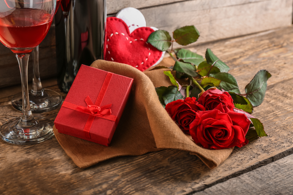 St. Valentines Day concept. Wine, roses and gift box on wooden table