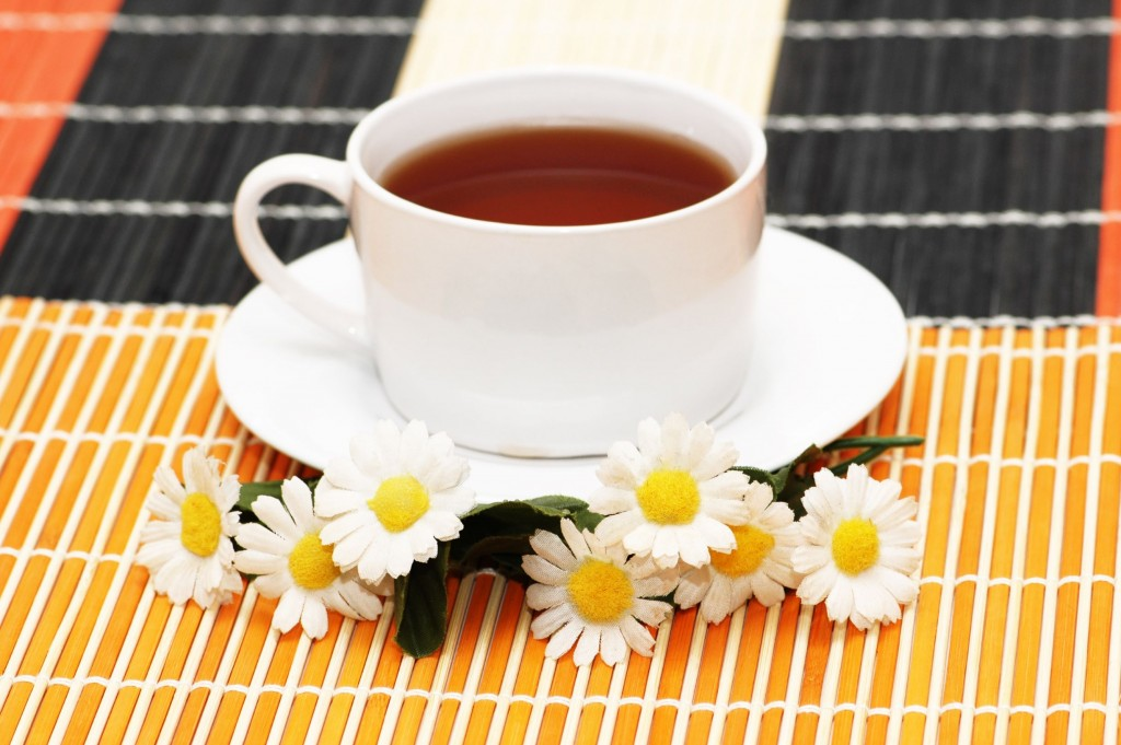 Cup of tea with herbs and daisy
